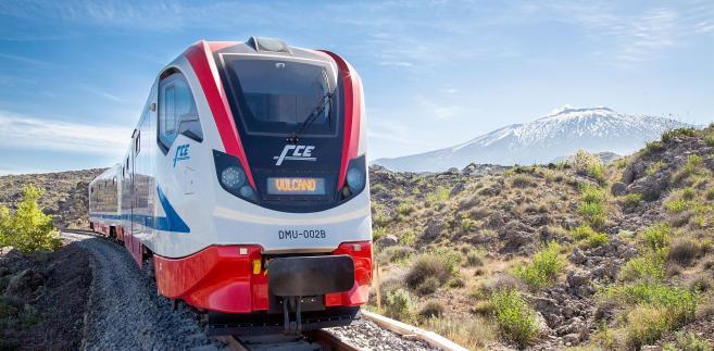Pociąg Vulcano Newagu dla przewoźnika FCE. W tle wulkan Etna