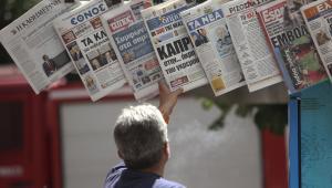 Przechodzień ogląda gazety na ulicy w Atenach