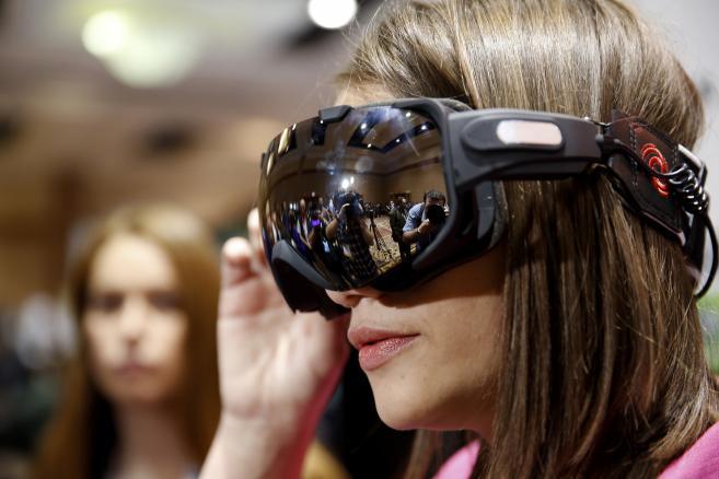 Jedna z dziennikarek przymierza zimowe sportowe gogle Liquid Image OPS (Operation Powder Search) z wbudowaną kamerą podczas spotkania dla prasy przed rozpoczęciem Consumer Electronics Show (CES 2014) w Las Vegas, 5.01.2014.