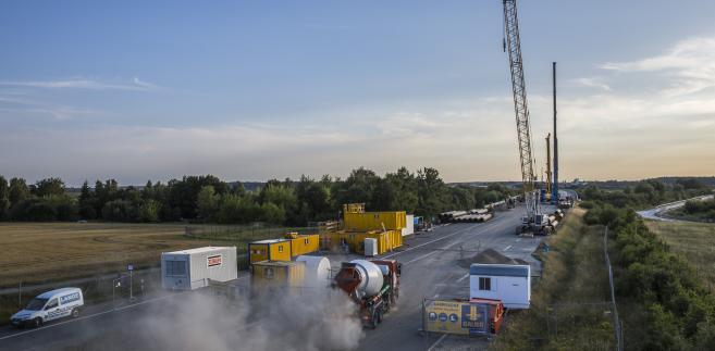 Pracownicy stoją obok betonomieszarki podczas trwających prac naprawczych na autostradzie A20 niedaleko Tribsees, Niemcy, w środę, 1 sierpnia 2018 roku. Fotograf: Rolf Schulten / Bloomberg