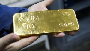 Robotnik trzyma sztabkę złota w hucie KGHM w Głogowie